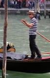 Glimlachende jonge gondelier in traditionele kleding op zijn gondel op Grand Canal Royalty-vrije Stock Foto's