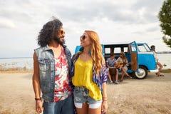 Glimlachende jonge hippievrienden dichtbij minivan auto Royalty-vrije Stock Afbeeldingen