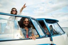 Glimlachende jonge hippievrienden over minivan auto Royalty-vrije Stock Foto's