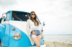 Glimlachende jonge hippievrouw met minivan auto Stock Foto