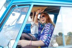 Glimlachende jonge hippievrouwen die minivan auto drijven Stock Foto