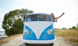 Glimlachende jonge hippievrouwen die minivan auto drijven Stock Foto's