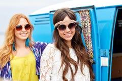 Glimlachende jonge hippievrouwen over minivan auto Stock Afbeeldingen