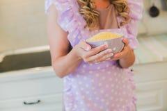 Glimlachende jonge huisvrouw Het koken baksel in de keuken royalty-vrije stock foto
