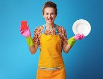 Glimlachende jonge huisvrouw met spons en plaat op blauw stock foto