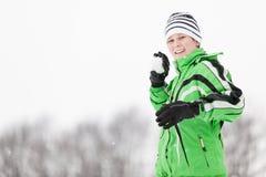 Glimlachende jonge jongen die doel met een sneeuwbal nemen Royalty-vrije Stock Foto's