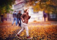 Glimlachende jonge jongen, jong geitje die pret in het park van de de herfststad onder gevallen bladeren hebben Stock Foto's