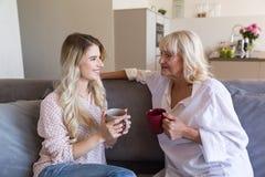 Glimlachende jonge kleindochter die aan haar grootmoeder spreken stock afbeelding
