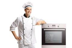 Glimlachende jonge mannelijke chef-kok die zich naast een oven bevinden royalty-vrije stock foto's