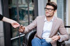 Glimlachende jonge mens die door creditcard in openluchtkoffie betalen royalty-vrije stock foto