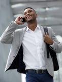 Glimlachende jonge mens die en op mobiele telefoon lopen spreken Stock Foto