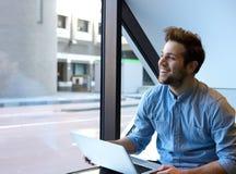 Glimlachende jonge mens die laptop met behulp van stock afbeelding