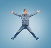 Glimlachende jonge mens die in lucht springen Stock Afbeeldingen