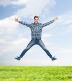 Glimlachende jonge mens die in lucht springen Royalty-vrije Stock Fotografie