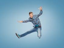 Glimlachende jonge mens die in lucht springen Stock Foto's