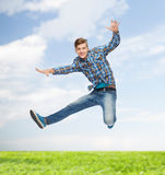 Glimlachende jonge mens die in lucht springen Royalty-vrije Stock Afbeeldingen