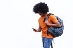 Glimlachende jonge mens die met zak en mobiele telefoon lopen Royalty-vrije Stock Foto