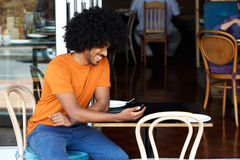 Glimlachende jonge mens die mobiele telefoon met behulp van bij koffie Stock Afbeelding