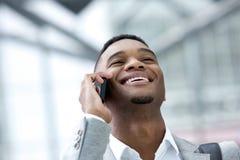 Glimlachende jonge mens die op mobiele telefoon spreekt Stock Fotografie