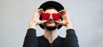 Glimlachende jonge mens die rode harten op ogen houden stock foto