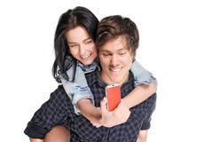 Glimlachende jonge mens die zijn mooi meisje vervoert per kangoeroewagen dat de telefoon bekijkt Royalty-vrije Stock Afbeelding