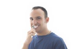 Glimlachende jonge mens die zijn tanden borstelt royalty-vrije stock foto
