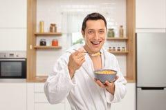 Glimlachende jonge mens in een peignoir die graangewas van een kom in een keuken eten stock foto