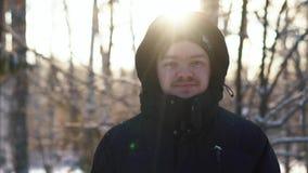 Glimlachende jonge mens in een zwart jasje met kap die in de winterbos blijven en de camera bekijken Close-up stock footage