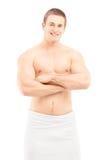 Glimlachende jonge mens in handdoek het stellen na douche Stock Afbeeldingen