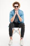 Glimlachende jonge mens in hoed en zonnebril die op stoel zitten Royalty-vrije Stock Afbeelding