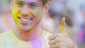 Glimlachende jonge mens in kleurenpoeder die duimen tonen die, Holi-festival vieren stock footage