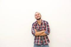 Glimlachende jonge mens met baard die zich tegen witte muur bevinden Royalty-vrije Stock Fotografie