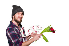 Glimlachende jonge mens met een baard met decoratieve woordliefde en rode die tulpen op witte achtergrond wordt geïsoleerd Royalty-vrije Stock Afbeelding