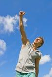 Glimlachende jonge mens met zijn wapen dat in vreugde wordt opgeheven Stock Fotografie