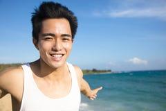 glimlachende jonge mens op het strand Stock Foto
