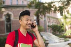 Glimlachende jonge mens op mobiele telefoon Royalty-vrije Stock Afbeeldingen