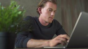Glimlachende jonge mens van bedrijfszitting bij computer en het typen bij laptop berichten Het knappe zakenman texting op a stock footage