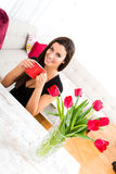 Glimlachende jonge mooie vrouw die van een kop van koffie genieten Stock Afbeeldingen