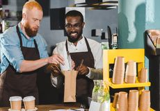 glimlachende jonge multi-etnische eigenaars die van koffiewinkel orde zetten royalty-vrije stock afbeeldingen
