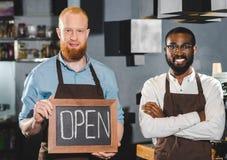 glimlachende jonge multi-etnische eigenaars van koffiewinkel met bord met het van letters voorzien stock fotografie