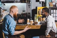 glimlachende jonge multiculturele eigenaars die van koffiewinkel en bij lijst met laptop spreken zitten royalty-vrije stock fotografie