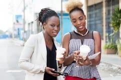 Glimlachende jonge onderneemsters die dozen melk delen Stock Fotografie