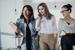Glimlachende jonge onderneemsters die in formele slijtage samen in modern bureau lopen Stock Afbeeldingen
