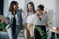 Glimlachende jonge onderneemsters die in formele slijtage samen in modern bureau lopen Stock Fotografie