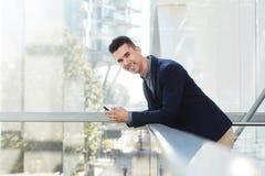 Glimlachende jonge ondernemer die zich met slimme telefoon bevinden Royalty-vrije Stock Fotografie