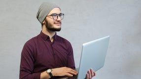 Glimlachende jonge peinzende laptop van de kerelholding, over witte geweven achtergrond stock afbeelding