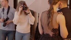 Glimlachende jonge professionele fotografen die in de studio stellen, houden zij digitale camera's stock footage