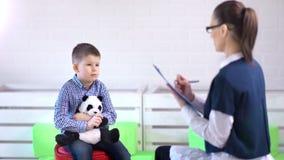 Glimlachende jonge professionele vrouwenpsycholoog die met weinig geestelijke gezondheid van de jongenszorg spreken stock video