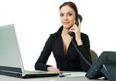 Glimlachende jonge receptionnist die bureautelefoon met behulp van Stock Fotografie