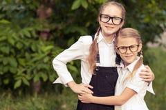 Glimlachende jonge schoolkinderen in een school eenvormig tegen een boom Royalty-vrije Stock Afbeelding